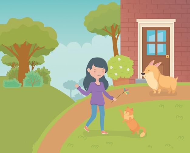 Mujer con lindo gatito y perro en el jardín de la casa