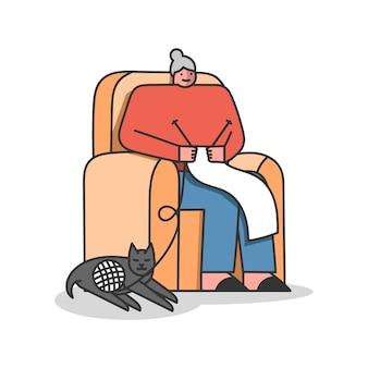 Mujer mayor está tejiendo sentado en un cómodo sillón