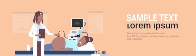 Mujer médico visitante haciendo ecografía del feto en el monitor digital consulta de ginecología