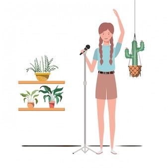 Mujer con micrófono con soporte y plantas de interior en perchas de macramé