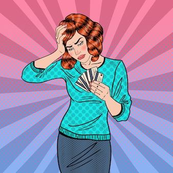 Mujer molesta del arte pop con tarjetas de crédito tiene dolor de cabeza.