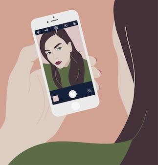 Mujer morena joven sosteniendo smartphone y haciendo foto selfie en cámara frontal.