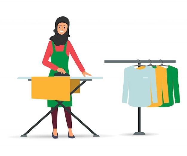 La mujer musulmana o árabe presiona la ropa con hierro.