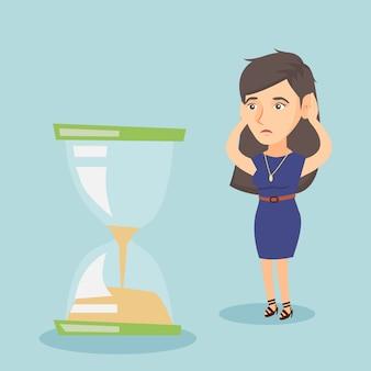 Mujer de negocios desesperada mirando el reloj de arena.