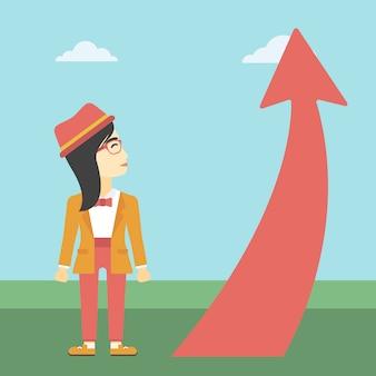 Mujer de negocios que mira la flecha que sube.