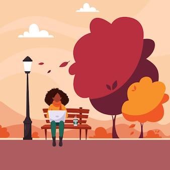 Mujer negra con portátil sentado en un banco en el parque otoño. concepto de trabajo autónomo y remoto. en estilo plano.