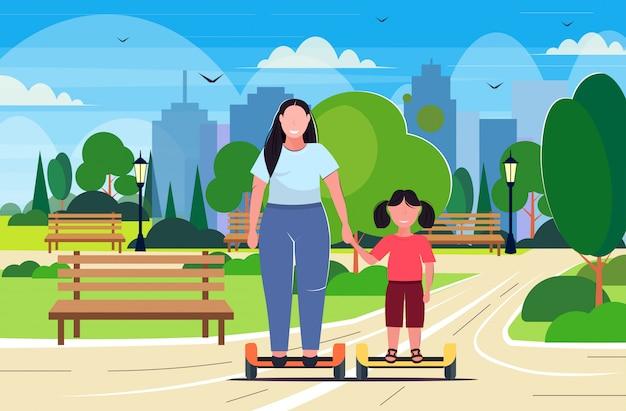 Mujer con niño montar auto equilibrio scooter madre e hija en gyroscooter eléctrico divirtiéndose parque público paisaje urbano fondo obesidad concepto integral horizontal