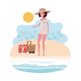 Mujer en la orilla de la playa con cesta de picnic.