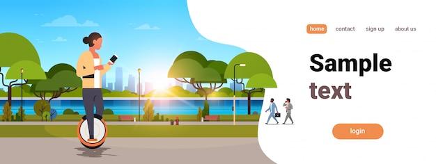 Mujer paseo mono rueda eléctrica con smartphone