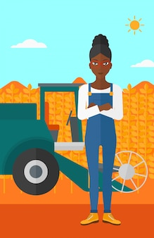 Mujer de pie con cosechadora en el fondo.