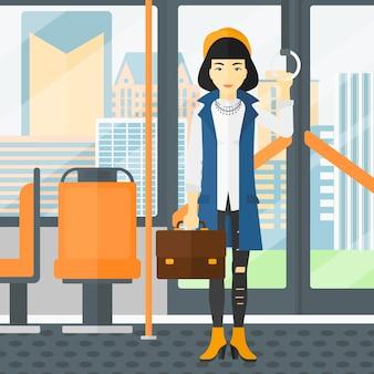 Mujer de pie dentro del transporte público.