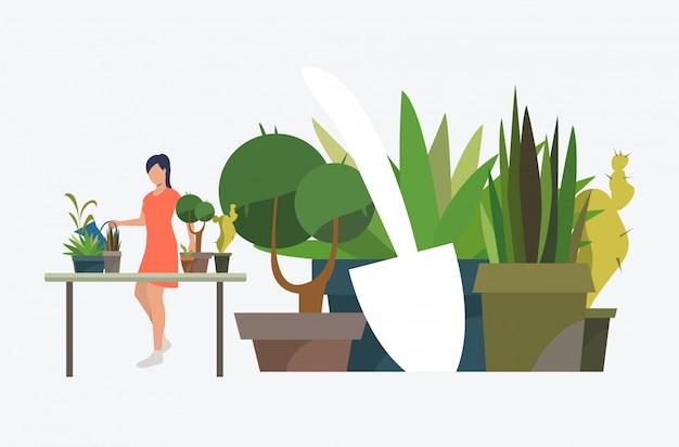 Mujer de pie en la mesa y creciendo plantas de interior en macetas