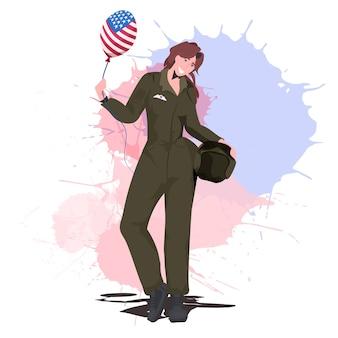 Mujer piloto en uniforme sosteniendo globo con bandera de ee.uu., feliz día del trabajo