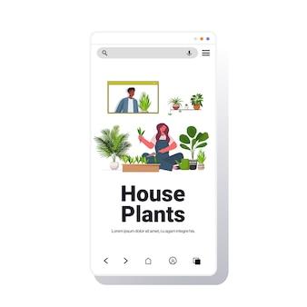 Mujer plantar plantas de interior en maceta chica discutiendo con un amigo afroamericano durante la videollamada espacio de copia de la pantalla del teléfono inteligente