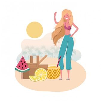 Mujer en la playa con cesta de picnic