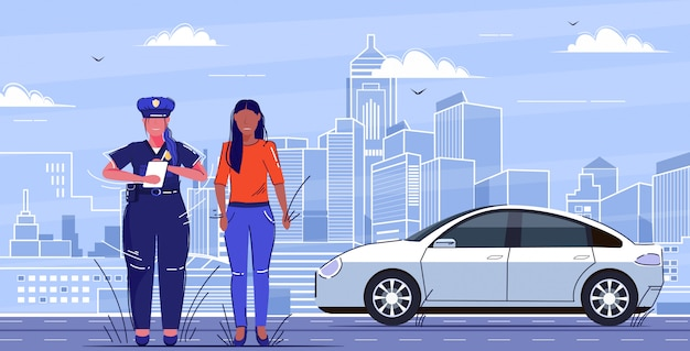 Mujer policía escribiendo informe multa de estacionamiento o multa por exceso de velocidad para triste mujer afroamericana conductor concepto de normas de seguridad vial tráfico plano paisaje urbano de longitud completa