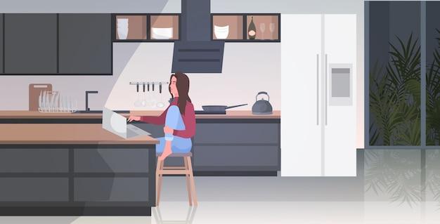 Mujer profesional independiente sentado en el mostrador trabajando en la computadora portátil quedarse en casa pandemia de coronavirus cuarentena
