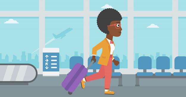 Mujer que camina con la maleta en el aeropuerto.