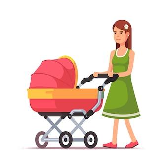 Mujer que camina con su niño en un cochecito de niño rosado