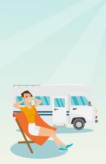 Mujer que se sienta en una silla delante de la autocaravana.