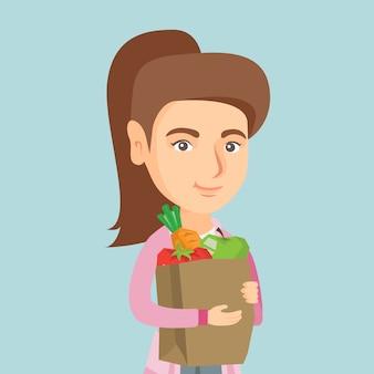 Mujer que sostiene el bolso de compras con la comida sana.