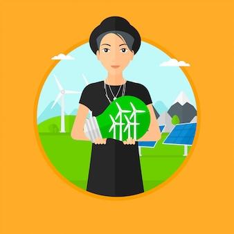 Mujer que sostiene la bombilla con turbinas de viento dentro.