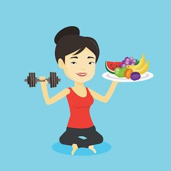 Mujer sana con frutas y pesas.