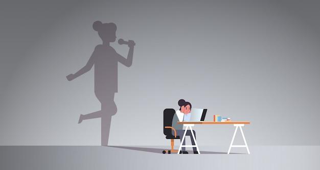 Mujer sentada en el lugar de trabajo usando laptop