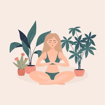 Mujer sentada en una posición de loto cerca de las macetas con plantas tropicales en una luz