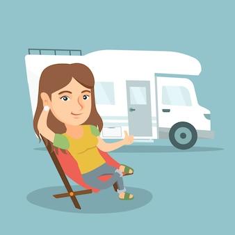 Mujer sentada en una silla delante de autocaravana.