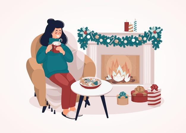 Mujer sentada en una silla con una taza junto a la chimenea y cajas de regalo