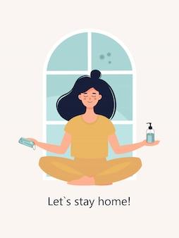 La mujer se sienta en la posición de loto en casa con mascarilla y desinfectante y texto vamos a quedarnos en casa.