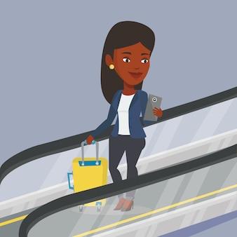 Mujer con smartphone en escaleras mecánicas en el aeropuerto.