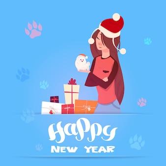 Mujer con sombrero de santa con lindo perro pomerian vacaciones de invierno 2018 banner año nuevo diseño de tarjeta de felicitación