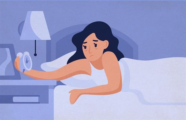 Mujer soñolienta acostada en la cama y mirando el despertador por la noche