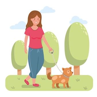 Mujer sonriente paseando al perro en el parque