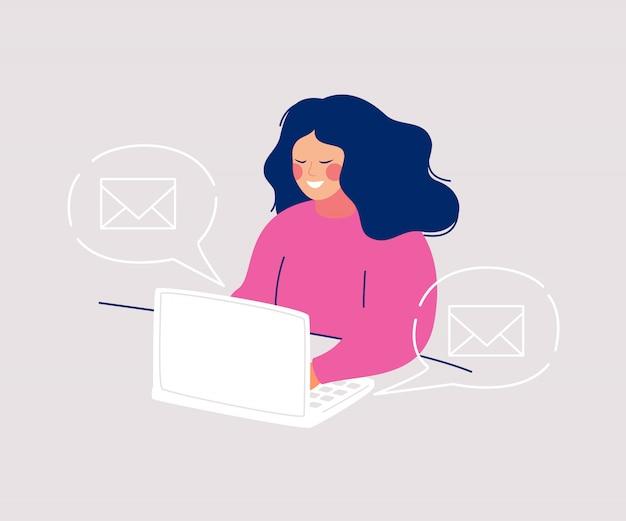 Mujer sonriente sentada en la computadora escribiendo mensajes e íconos sobres flotando en burbujas de discurso