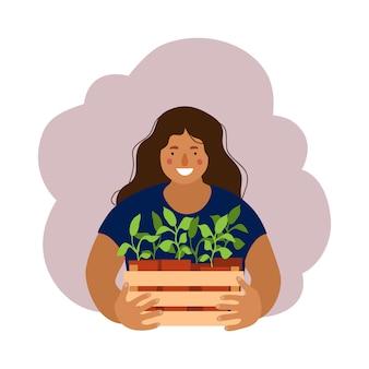 Mujer sosteniendo una caja con plántulas de jardín.