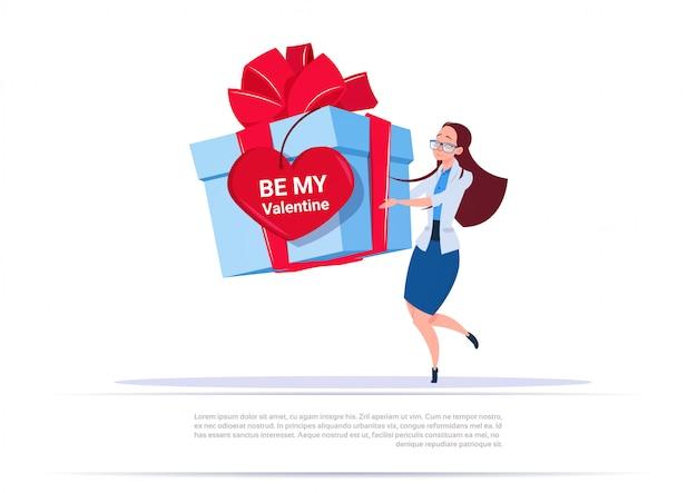 Mujer sosteniendo una gran caja de regalo con etiqueta de forma de corazón be me valentine saludo sobre fondo de plantilla