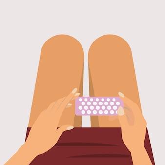 Mujer sosteniendo píldoras anticonceptivas en la habitación de la cama