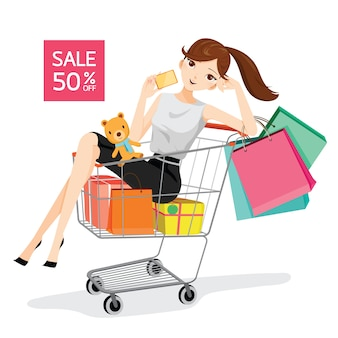 Mujer sosteniendo tarjetas y bolsas de compras sentado en el carrito de la compra