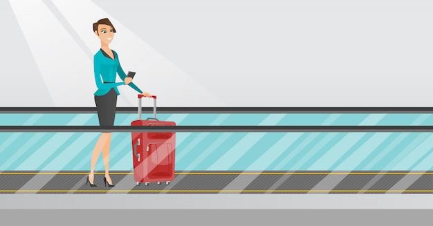 Mujer con teléfono inteligente en la escalera mecánica en el aeropuerto