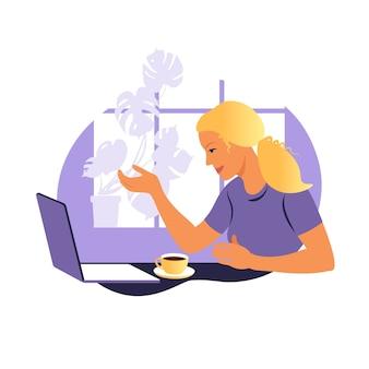 Una mujer trabaja y se comunica en una computadora portátil, sentada en una mesa en casa con una taza de café y papeles.