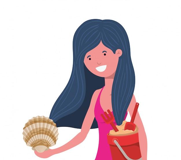 Mujer con traje de baño y cubo de arena.