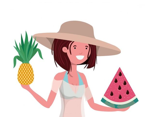 Mujer con traje de baño y frutas tropicales en la mano.