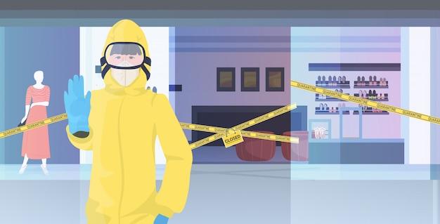 Mujer en traje de materiales peligrosos que muestra el centro comercial de gesto de parada con cinta amarilla cuarentena pandémica coronavirus
