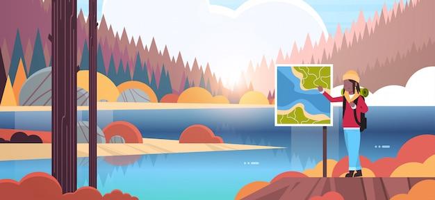 Mujer turista excursionista con mochila mirando mapa de viaje mujer viajero planificación ruta senderismo concepto amanecer otoño paisaje naturaleza río bosque montañas fondo horizontal