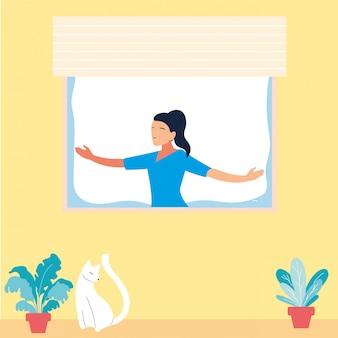 Mujer en la ventana haciendo ejercicios de baile en casa