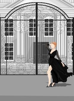 Mujer en vestido negro posando delante de las puertas del castillo