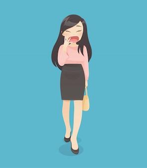 La mujer en vestido de trabajo está bostezando